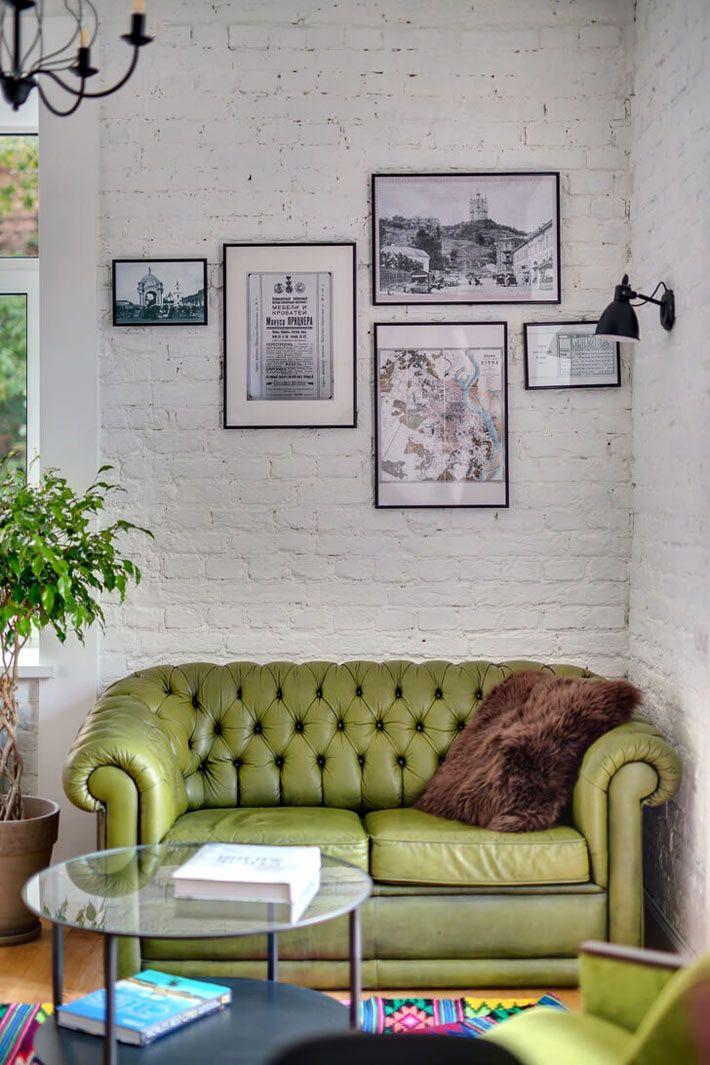 Белая кирпичная стена и зеленый диван как изюминка гостиной комнаты