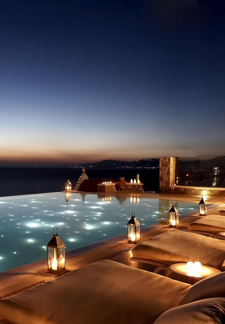 The infinity pool at Bill & Coo Suites in Mykonos looks as though it merges with the waters of the bay. In the evening lanterns placed around the pool which is illuminated by dozens of tiny led lights, mirroring the cosmos www.mediteranique.com/hotels-greece/mykonos/bill-coo-suites-and-lounge/