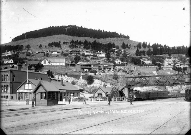 The Railway yards, Lyttelton, showing the signal box and the partially obscured goods office. A train can be seen puffing smoke on one of the tracks. There are houses on the hill overlooking the railway yards. Taken by Frederick George Radcliffe in 1916.