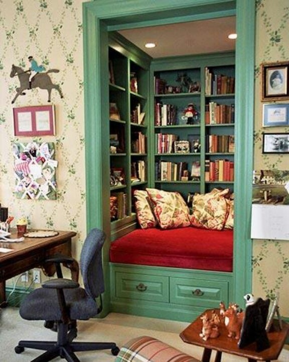 nook with green bookcase walls and red velvet daybed