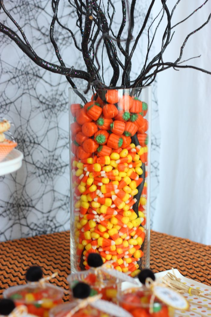Place a paper towel roll in the middle of a tall columnar vase; fill outer ring with candy corn & pumpkins; insert branches (spray painted black) - quick & easy centerpiece!