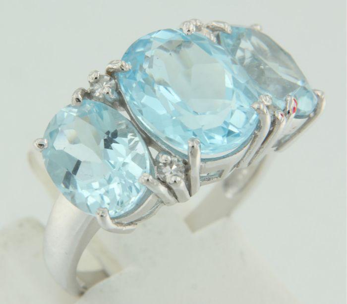 14k witgouden ring bezet met drie blauwe topazen - diamanten 010ct - ringmaat 1725 (54)  De bovenzijde van de ring is 11 cm breed en 66 mm hoogGewicht 50 gram Bezet met- 1 x 11 cm x 90 mm ovaal facet geslepen blauwe topaas totaal circa 340 caraat- 2 x 91 mm x 70 mm ovaal facet geslepen blauwe topaas totaal circa 500 caraat totaal gewicht 840 caraatkleur hemels blauwzuiverheid SIEdelstenen zijn vaak behandeld om kleur of helderheid te verbeteren. Dit is niet onderzocht bij dit specifieke…