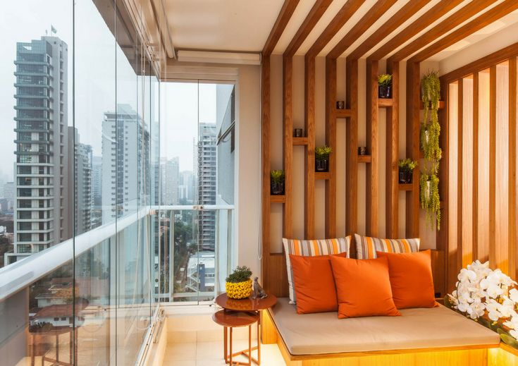 Vem ver a decoração desse apartamento, com varanda e sala integradas. Na varanda, ripas de madeira, futton e vasos na parede - ideal para relaxar!