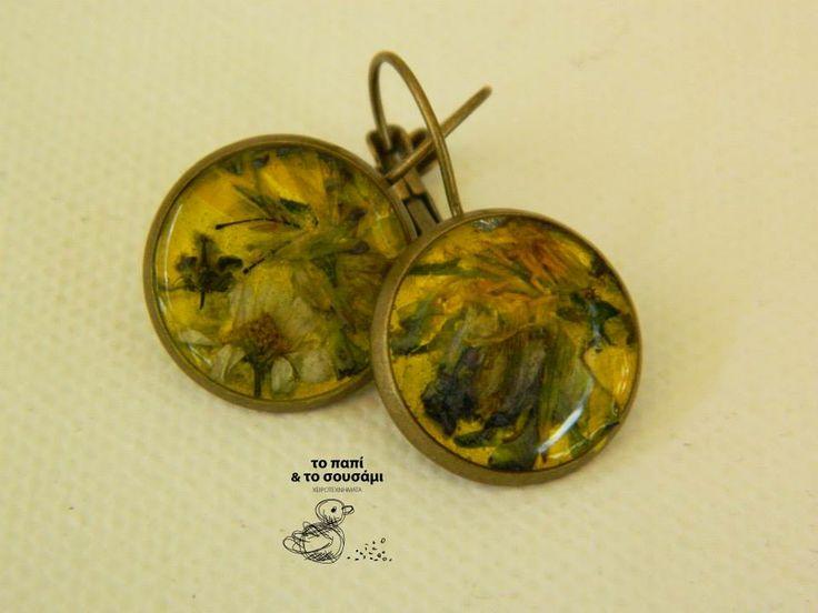 Στρογγυλά μπρούτζινα κρεμαστά σκουλαρίκια με μικροσκοπικά αληθινά λουλούδια,μαζεμένα με προσοχή, σε κίτρινο φόντο. Round bronze resin earrings with natural tiny flowers collected with care on a yellow background.