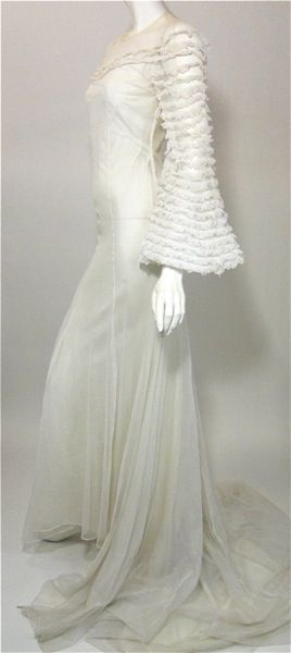 Superb 1930s white mesh netting bridal gown. Voluminous ruffled sleeves, ruffled across upper bust where lining ends leaving neckline sheer. Ties in back at nape with cord tie, side metal snaps. Long train with 2 loops to pull up while walking and to hang.