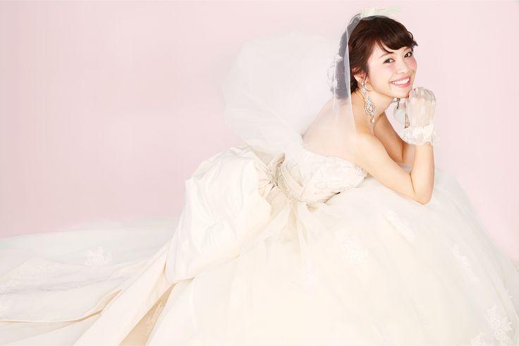 【THE HANY 2015 ステファニー】見頃に施されたインドビジューレースと、スカートに柄置きされたリバーレースという贅沢な素材使いが秀逸なエンパイアスタイルのウェディングドレス。大きなバックリボンは重厚感があり、クラシカルな佇まいの花嫁様に。