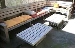 Grote L-vormige bank (450 x 180 cm) plus twee lage tafels van pallets.