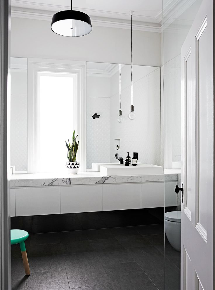 """""""We wanted the window as the centrepiece in the bathroom, so we created a long marble bench with sinks either side,"""" Johanna says. The door adds a traditional touch to the modern space."""