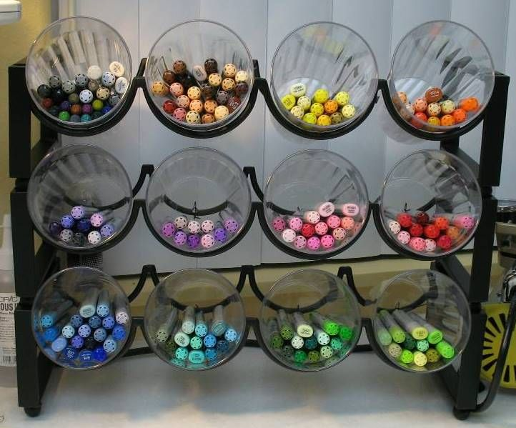 markers stored in plastic cups wired to a wine rack