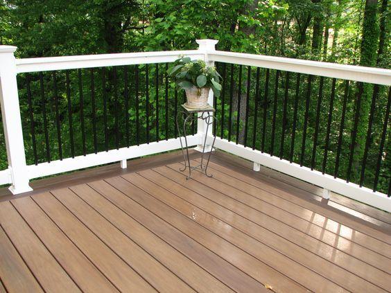 Longevity black aluminum balusters with white PVC #deck railing and WOLF PVC decking amberwood flooring.