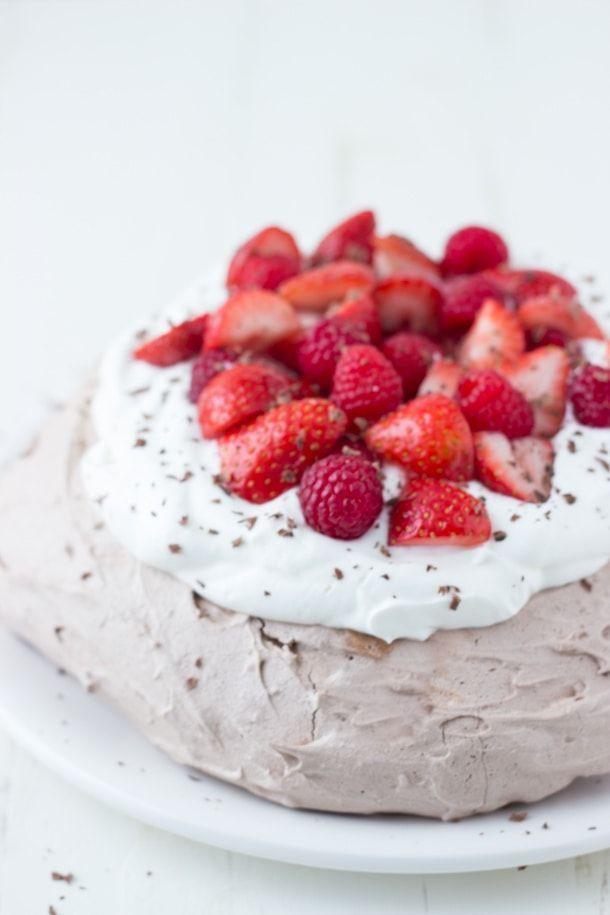 A stunning chocolate pavlova recipe topped with strawberries and cream for an easy dessert. #chocolate #pavlovas