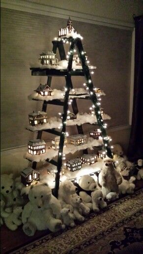 Christmas village displayed on old wooden ladder.