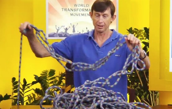 Tim Macartney-Snape presenting Part 2 of Video Series 1 titled 'The World Transformation Movement'. Here he is using a climbing rope to demonstrate an analogy about how something can look impenetrable until you find the unlocking point - much like the issue of the human condition.