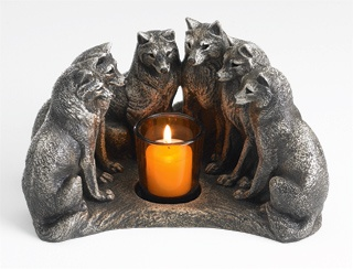 """Council of Wolves Candleholder In Celtic tradition, the wolf is associated with intuition and learning. Six wolves sit in a semi-circle to contemplate the flames and share the lessons of the pack. 9"""" across, 5"""" high. Cast stone, for indoor use only. Candle and holder included"""