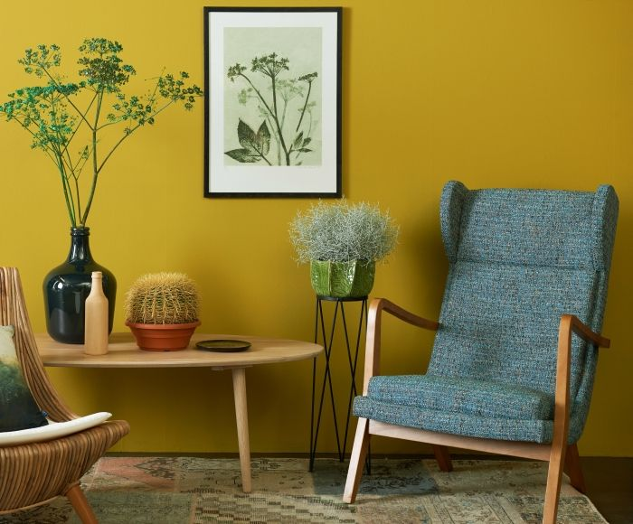 Dit oker groen-geel is bekend uit de jaren 80, als textielkleur, en nu als vernieuwende kleur in een botanische kleurkaart. Deze felle kleur vraagt om een rustige combinatie met houttinten. De afgeronde vormen van het meubilair geven dit plaatje een zacht en natuurlijk gevoel mee. Het donkerblauw van de stoel zorgt kleur technisch voor een mooi contrast.