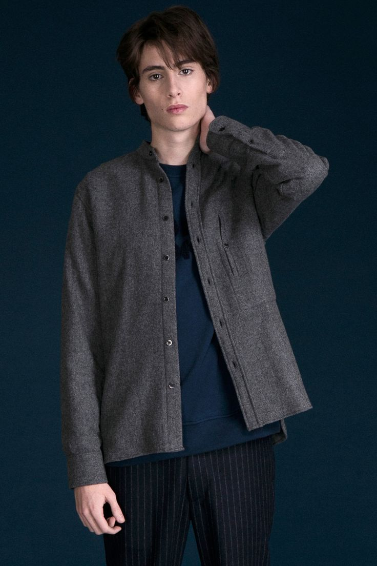 Chemise en laine grise.  Col officier.  Poche poitrine verticale boutonnée.  Fabriquée au Portugal.  80% Laine 20% Polyamide.