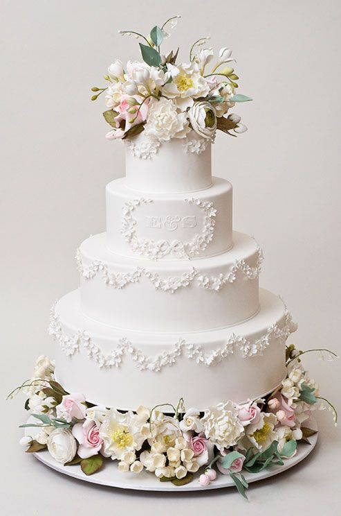 Delicate garlands and pastel colored blooms make this classic all- white wedding cake a true favorite.