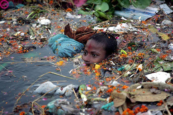 Un petit garçon se baignant dans une eau envahie de déchets en Inde A child bathing in water invaded waste in India