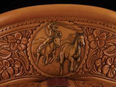 Three dramatic scenes of bronc riders adorn a Rick Bean saddle that begs to be ridden. Built on a 16-inch Wade tree, the 8-string saddle has a wide, hand-carved floral border and bucking rolls, highlighted by sterling silver conchas by Scott Hardy. Price: $14,000 From the The Traditional Cowboy Arts of America 2013 Exhibit http://tcowboyarts.org/tcaa-2013-exhibit-at-the-cowboy-museum-okc/