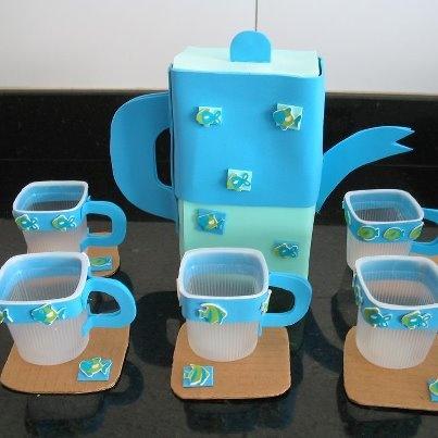 Juego de café para la cocinita de clase se ha hecho con material de deshecho. Las tacitas son envases de flan vacíos, al que hemos enganchado con cola una tira decorativa de goma eva y una asa del mismo material. Los platitos realizados con un trozo de cartón en el que se ha pegado el motivo decorativo del pez para que haga juego con las tazas.      Finalmente la cafetera hecha con un envase de tetrabrick forrado de papel de color (del mismo color que la goma eva pero varios to