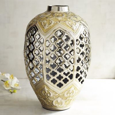 We've taken a modern material and created the look of an antiqued classic piece. Our vase, with quatrefoil cutouts in a burnished silver with golden accents, is made of  rust-resistant lightweight aluminum.  Dynamic on its own or fill with dry florals for a stunning centerpiece.