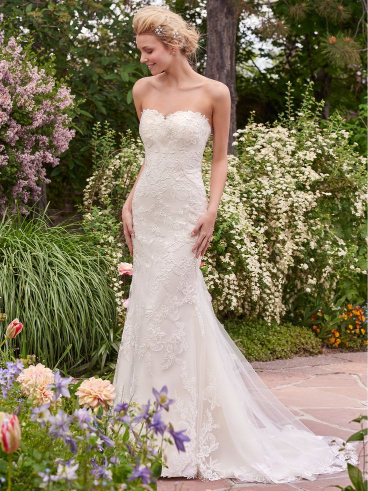 Sandra Wedding Dress | Rebecca Ingram. Soft lace appliqués evoke classic romance in this fit-and-flare, complete with a subtle sweetheart neckline and illusion scoop back accented in lace. Finished with covered buttons over zipper closure.