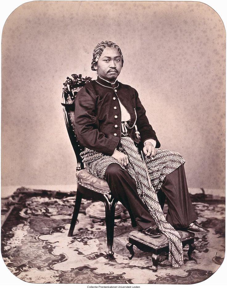 man in traditionele kledij zittend op stoel met de voeten op een bankje
