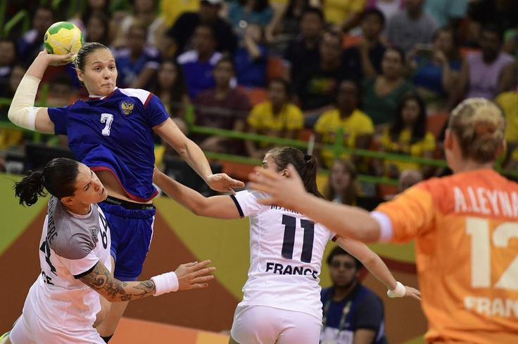 Russia's centre back Daria Dmitrieva (L) shoots past France's right back Alexandra Lacrabere (downL) during the women's Gold Medal handball match France vs Russia for the Rio 2016 Olympics Games at the Future Arena in Rio on August 20, 2016. / AFP / afp / JAVIER SORIANO