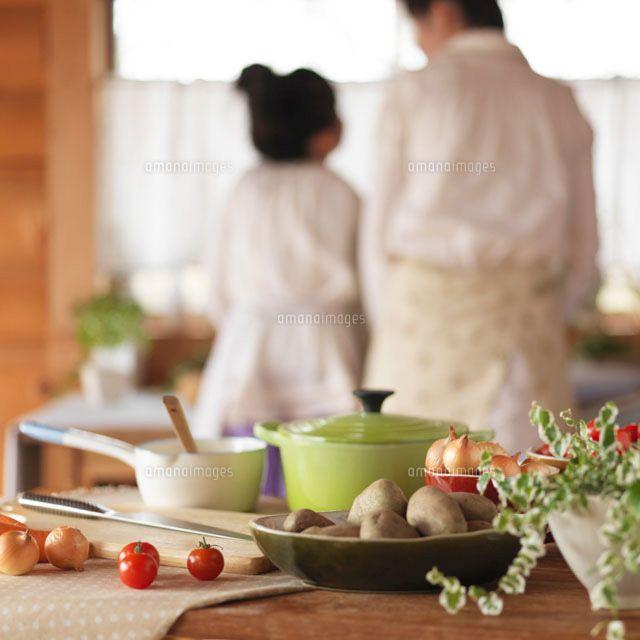 キッチンで一緒に料理をする母親と女の子の後姿 C Hororo Style