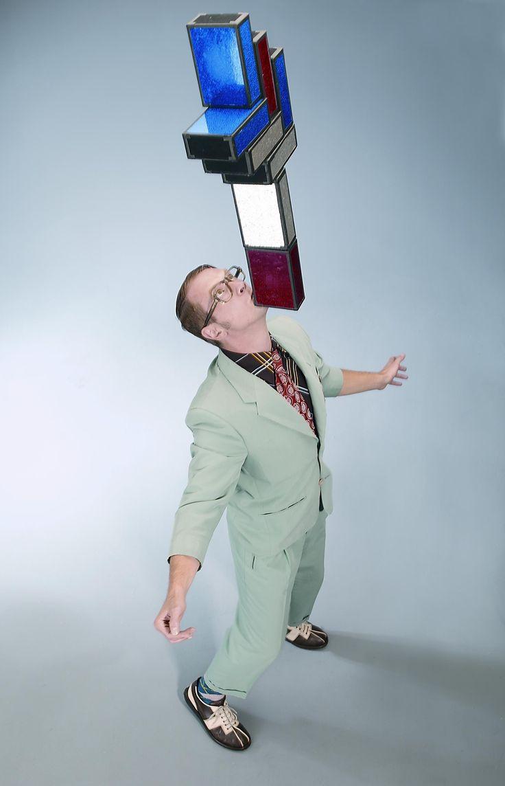 """Mit seinem Comedy-Charakter """"Willi Horstkötter"""" spielt Kleinkünstler Krawalli einen leicht verwirrten Herrn mittleren Alters,  der sein Publikum mit absurden Gags und spontaner Situationskomik überrascht. Der Komiker balanciert acht Zigarrenkisten frei stehend auf dem Kinn und präsentiert zwischendurch aberwitzige Parodien von klassischen Zaubertricks."""