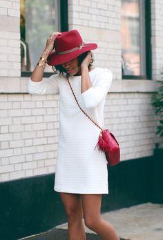 weißes gerade geschnittenes Kleid mit Reliefmuster, rote gesteppte Leder Umhängetasche, roter Wollhut, golden – Mona Stimper