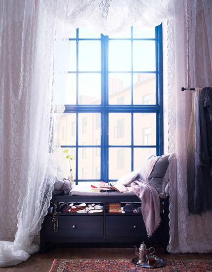 IKEA opbergbank met kussens voor een groot raam met kanten gordijnen