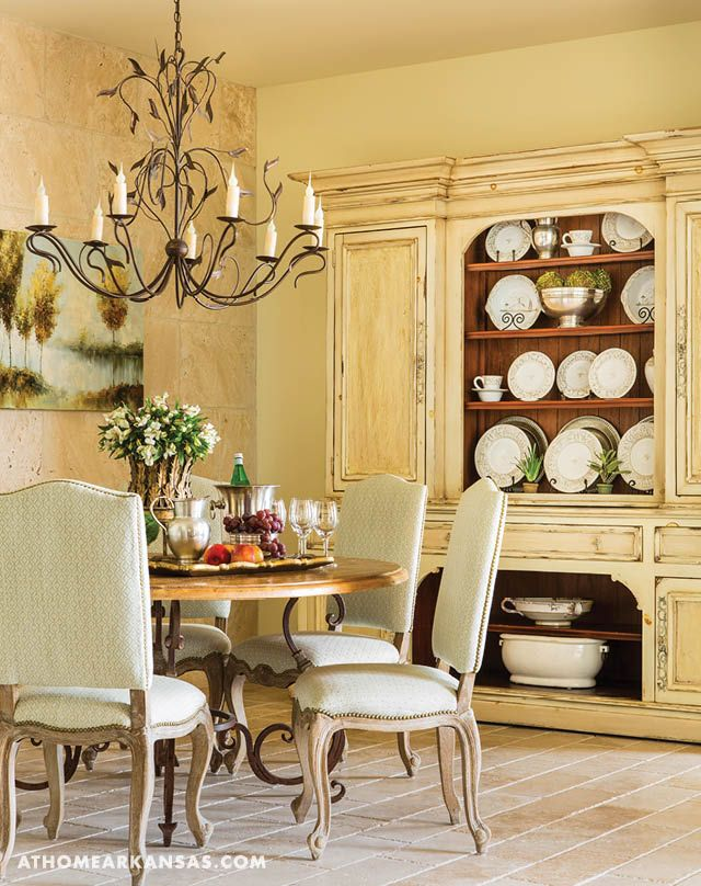 custom stone seen on the back wall and floor lends a refined european cottage feel to the homes formal dining room