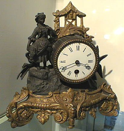 Antique Victorian mantle clock. Wonderful Victorian mantle clock made from iron and brass. Depicts a shepherdess standing next to a well house in the Baroque or Rocco style. Measures 10 inches by 10 inches.