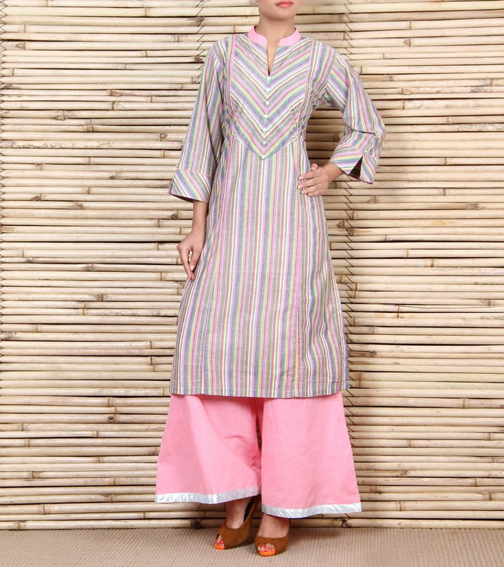 This is a cotton striped kurta with diagnol stripes on the yoke and sleeves eith a pink collar and piping on the frnt with silver buttons. It is paired with pink cotton palazzos with a silver patti on the bottom.