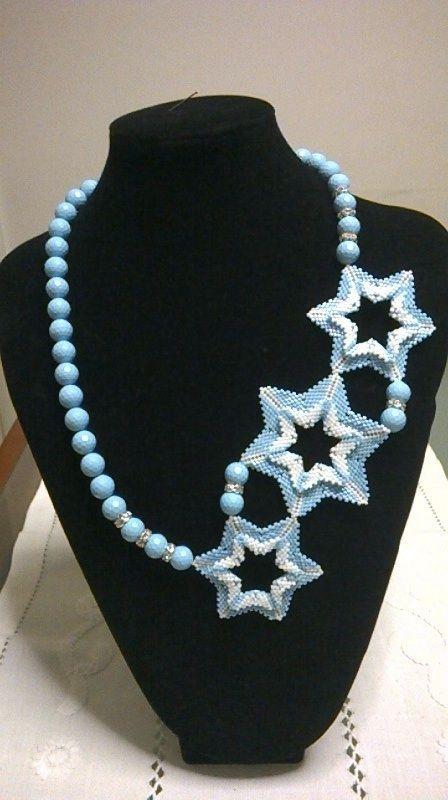 Collana Stella azzurra:  Collana realizzata con tre stelle a sei punte lavorate in peyote con microperline azzurre e bianche ed unite da perle azzurre e spaziatori in strass. Chiusura con moschettone argentato.
