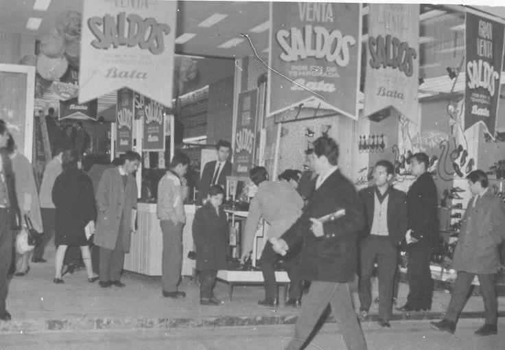 Santiago, Chile ca. 1965. En la vereda norte de la Alameda Bernardo O'Higgins, cerca de la Estación Central, vemos a los transeúntes y clientes fuera de una tienda Bata, viendo las ofertas de esa temporada