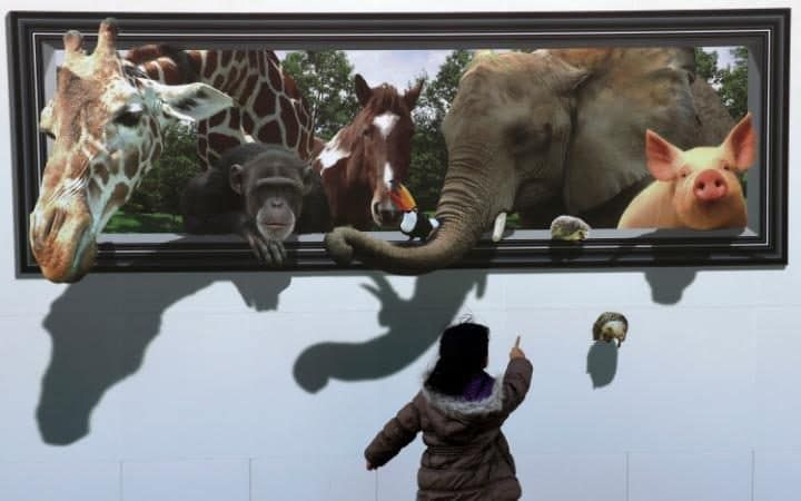 A girl looks at a 3D picture of animals drawn on the safety wall at a construction site of the archery venue for the Tokyo 2020 Summer Olympics in Japan