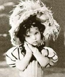 """Shirley Temple in Glad Rags to Riches / Glad Rags to Riches was released on February 5, 1933, and was distributed by Educational Film Exchanges. The 11-minute film stars Temple as Le Belle Diaperina, a Gay Nineties chanteuse at the Lullaby Lobster Palace who must decide whether to marry a rich nightclub owner or a country boy. The film features her first on-screen tap dance and song, """"She's Only a Bird in a Gilded Cage""""."""