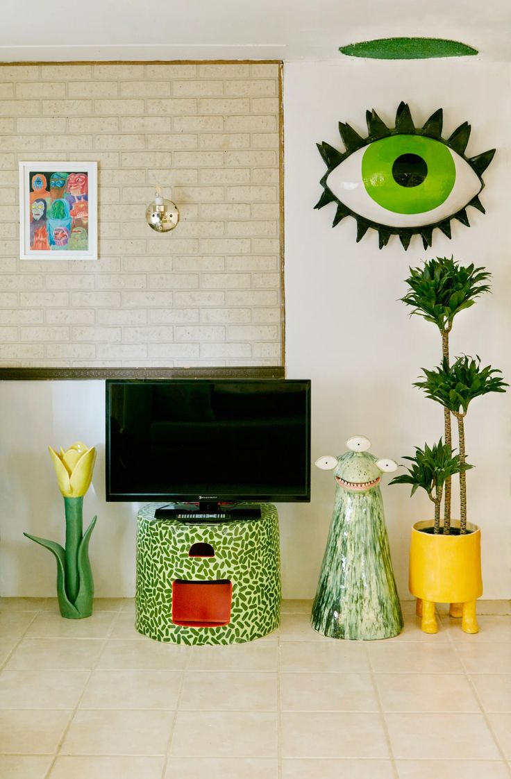 Green speckled ceramic TV stand next to yellow planter. On the wall is a ceramic eye sculpture Quirky Bedroom, Bedroom Decor, Quirky Living Room Ideas, Decor Room, Funky Home Decor, Eclectic Decor, Cool Room Designs, Décor Boho, Aesthetic Room Decor