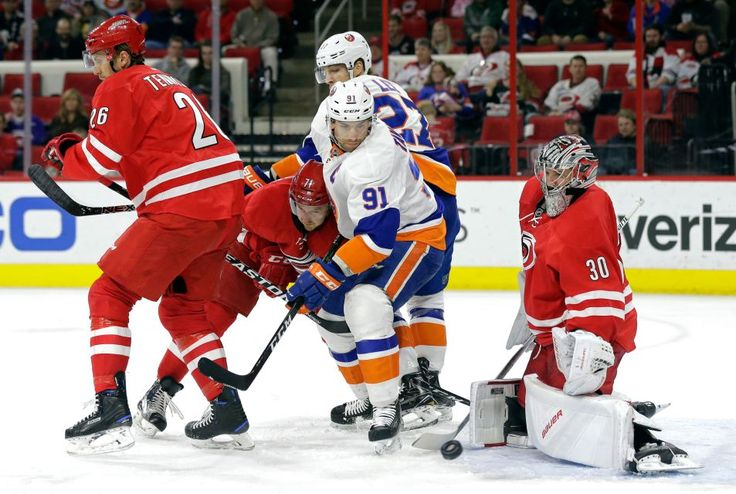 New York Islanders' John Tavares (91) and Anders Lee (27) try to score against Carolina Hurricanes goalie Cam Ward (30) as Hurricanes' Matt Tennyson (26) and Lucas Wallmark (71), of Sweden, defend during the first period of an NHL hockey game in Raleigh, N.C., Tuesday, March 14, 2017.