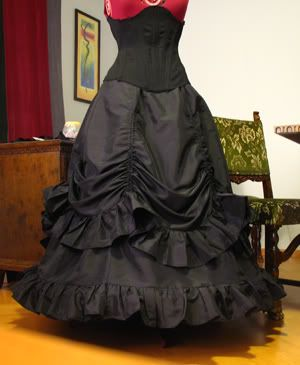 How to sew a Victorian style skirt with two layers, the top one being adjustable with string in the panels.  It's much easier than you would expect. Basically 2 six panel skirts with ruffles, the top one having strings sewn into the seam allowances. You can make a bustle by pulling up a couple in the back all the way to the top, wear it with the top layer all the way down, or pulled up part way as shown above.