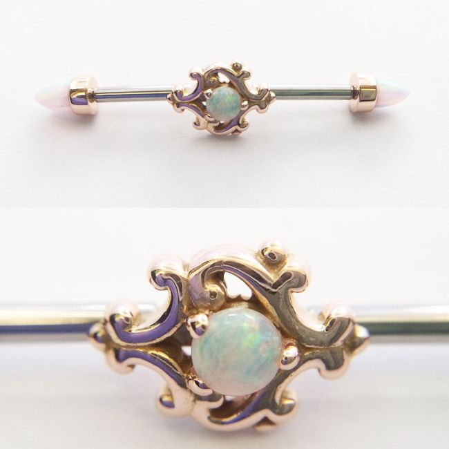 """14g industrial barbell with 14K rose gold """"Milano"""" Paloma swirl center piece and 14K rose gold white opal bullet cut ends."""