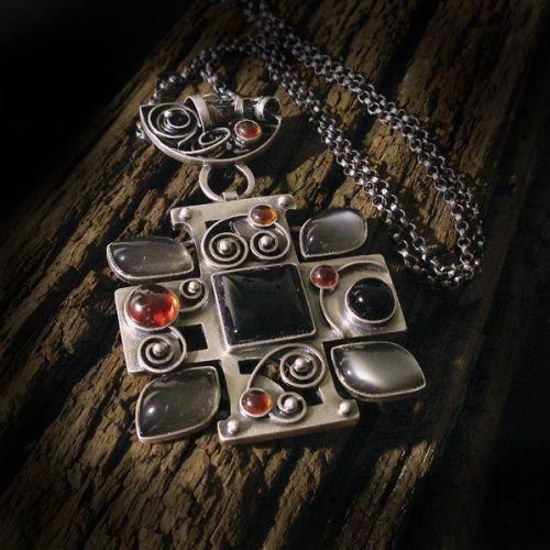 Jedyny w swoim rodzaju, prosty, ale bogato zdobiony, nowoczesny wisior/amulet, wykonany od podstaw ręcznie tradycyjnymi technikami złotniczym ze srebra pr. 925. Kamienie - onyksy, kamienie księżycowe i cyrkonie. Srebro postarzone i oksydowane. Długość ok. 7 cm, szerokość ok. 5 cm. Waga: 33 gr. Długość łańcuszka - 60 cm. Praca bardzo pracochłonna, wykonana w jednym egzemplarzu.