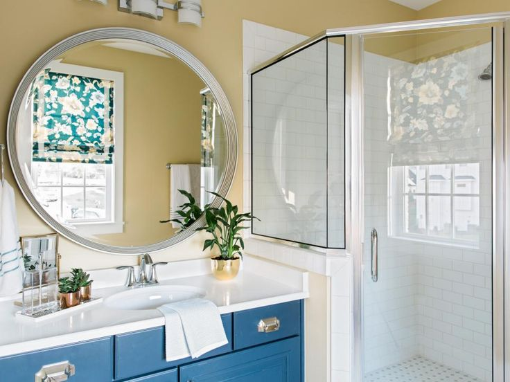Brilliant blue cabinetry and crisp white subway tile bring a modern touch into the bathroom, while a walk-in shower and sleek hardware add a spa-like vibe.