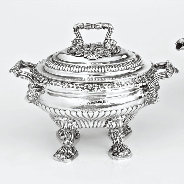 A Regency silver sauce tureen and cover, Paul Storr, London, 1815 on high acanthus feet, the part-gadrooned body engraved on each side with contemporary arms, shell, foliate and gadroon rim, crested cover, reeded handles rising from lion heads
