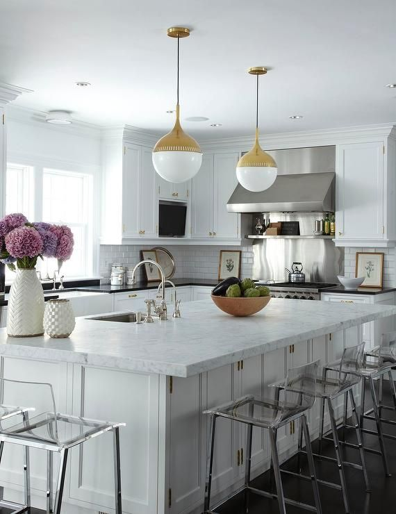 Amazing kitchen features a pair of Robert Abbey Jonathan Adler Rio Pendants in Antique Brass illuminating a large kitchen island fitted with cabinets and topped with white marble framing a stainless steel prep sink and two gooseneck faucets and Crate & Barrel Adra Vase and Rati Vase lined with clear counter stools, CB2 Vapor Counter Stools.