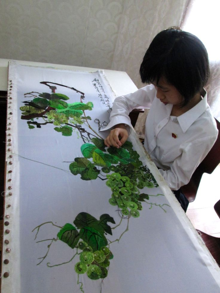 North Korean girl practicing sewing skills at the Mangyongdae Children Palace in  North Korea by Stanito