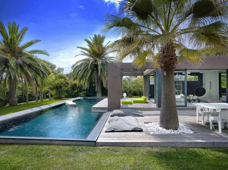 Hotels & Resorts:Amazing Outdoor Villa In France With Swimming Pool And Palm Tree Also Wooden Deck Design Ideas With Dining Set And Then This Remarkable Outdoor Villa Design Ideas With Swimming Pool Design At Backyard Outstanding Cozy Villa With Nicely Colorful and Lovely Landscaped in France