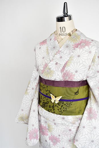 クリーム色地にクレパスで描いたような絣風のタッチ柔らかに愛らしく、重なりあう菊花が染め出された化繊の夏着物です。